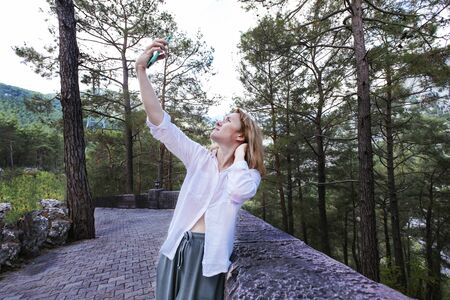 Portrait 40 years old woman with blond hair doing selfie by phone on beautiful nature background. Stock photography.