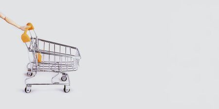 Banner with shopping cart and hand. Grocery shopping and sale concept. Black friday, online shopping and store concept. Sale discount. Background with copyspace. Creative design. Stock photography. Stok Fotoğraf