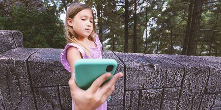 Portrait teenager girl with blond hair doing selfie by phone on beautiful nature background. Stock photography.