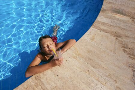 Beautiful teenager boy relaxing at swimming pool with cocktail. Kid having fun on summer vacation. Holiday and lifestyle concept Archivio Fotografico - 137952592