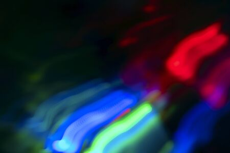 Abstract blur pattern of blue, green, red, yellow lights on isolated black background. Glitter texture christmas abstract backdrop. New Year light.