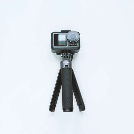 Chekhov, Russia - March 8, 2020: DJI Osmo Action and tripod isolated on white background. Action camera for photo and video. Editorial