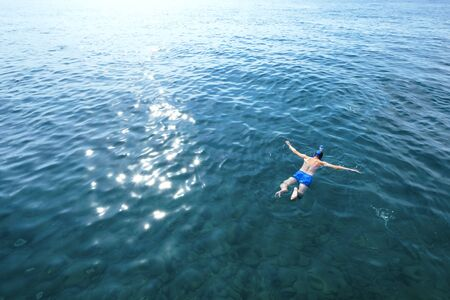 Young man in swimwear lying on blue water. Man in swimming mask relaxing in sea. Tropical summer vacation. Tranquility and peace. Person floating in ocean and watching fish