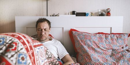 Man work and look at phone in bed. Work online from home. Quarantine, self isolation, depression, social distance, mental health concept. Stock photo.