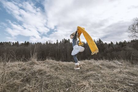 Happy girl rejoices autumn with yellow scarf. Young child playing outside. Sunny day activity. Happy, joyful kid outdoors. Having fun alone. Beautiful, scenic forest landscape. Picturesque scenery Imagens