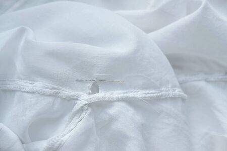 Mending clothes. Repairing fabric, shopping less concept. White dress with hole, thread and needle. Stock photo.