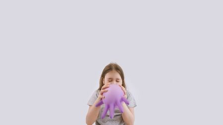 Young sad girl play with protective medical glove. Teenager with glove inflated like balloon. Quarantine, self isolation, depression, social distance, mental health concept. Stock photo.