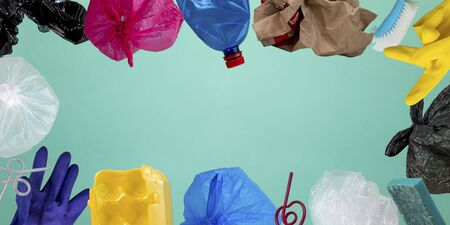 Color garbage. Plastic bags, bottle, crumpled paper bag, straws, rubber gloves, toothbrush, other trash on green background with copyspace. Ecology, environmental pollution concept.