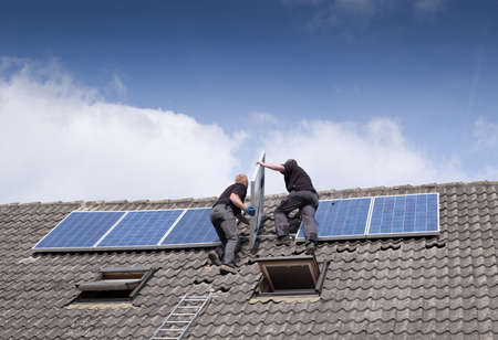solar panel roof: two men installing solar panels on rooftop