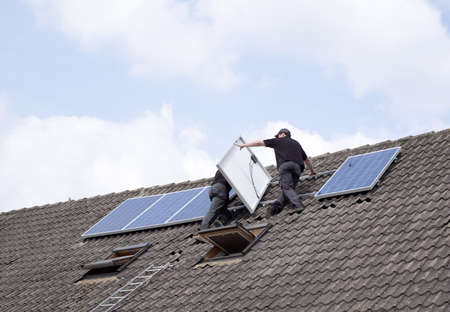 two men installing solar panels on rooftop  Stock Photo
