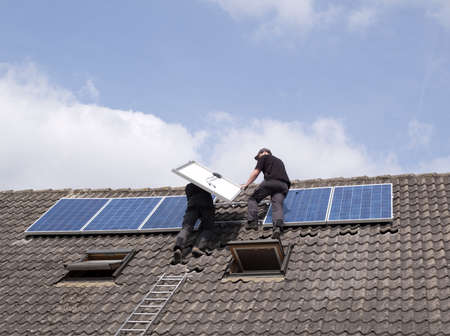 two men installing solar panels on rooftop