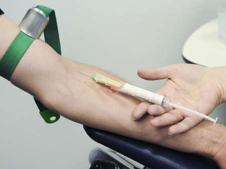 a nurse pricks a patient Stock Photo