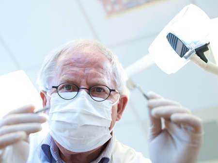 senior dentist looking at patients xray Stock Photo