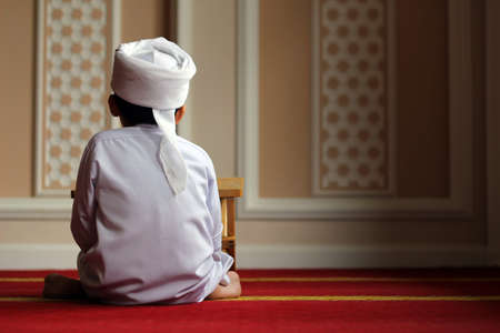 Young Boy with turban inside mosque photo
