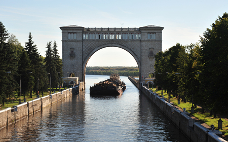 The cargo barge enters the navigable sluice on the Volga River in Uglich