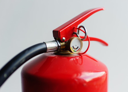red fire extinguisher on white background Foto de archivo