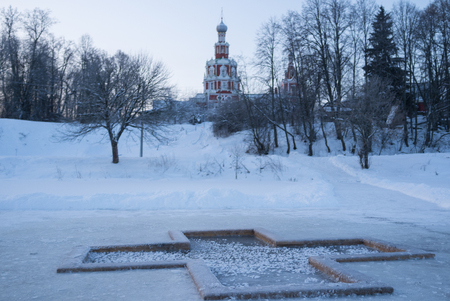 baptismal: Winter landscape. The font in the form of a cross on the background of the Orthodox Church.