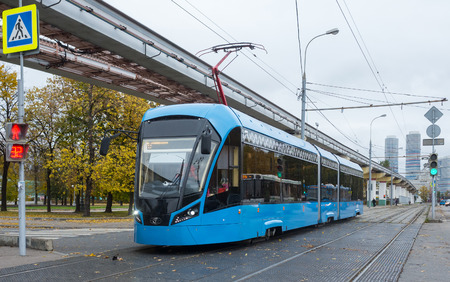 Blue electric tram on the background of the cityscape. Stock Photo - 90858157