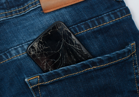 Mobile phone with a broken screen in the pocket of blue jeans. Stock Photo