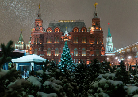 Christmas trees at the Manezh Square in Moscow on the background of the Historical Museum and the Kremlin Редакционное