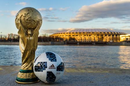 13 kwietnia 2018 Moskwa, Rosja Trofeum Mistrzostw Świata FIFA i oficjalna piłka FIFA World Cup 2018 Adidas Telstar 18 na tle stadionu Łużniki w Moskwie. Publikacyjne