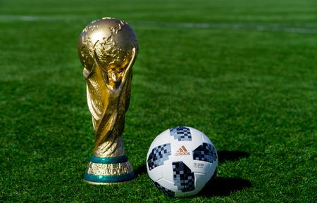 9. April 2018 Moskau, Russland Trophäe der FIFA Fussball-Weltmeisterschaft und offizieller Ball der FIFA Fussball-Weltmeisterschaft 2018 Adidas Telstar 18 auf dem grünen Rasen des Fußballfeldes.