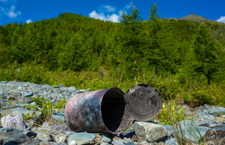 discarded can of canned food on the background of the mountain landscape