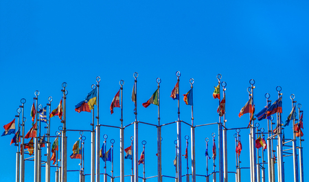 Flags of European countries on flagpoles against the blue sky. Reklamní fotografie