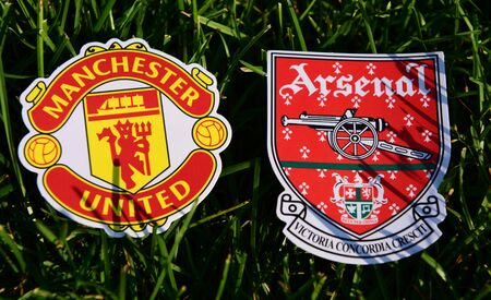 September 6, 2019 London, UK. Emblems of English football clubs rsenal F.C. London  and Manchester United on the green lawn grass.
