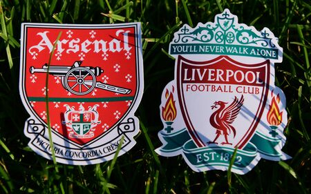 September 6, 2019 London, UK. Emblems of English football clubs rsenal F.C. London  and Liverpool on the green lawn grass. Editorial