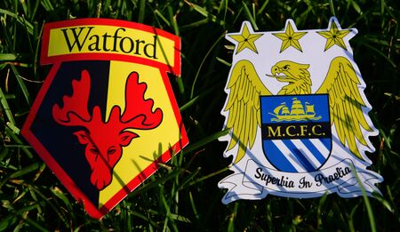 September 6, 2019 London, UK. Emblems of English football clubs Manchester City and Watford on the green lawn grass.