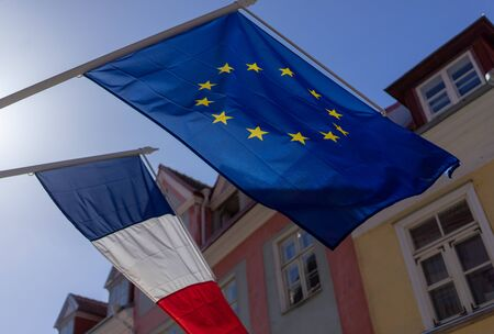 Flags of France and the European Union on the building against the blue sky on a bright Sunny day