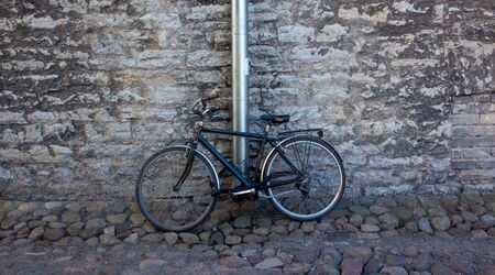 Black vintage bike at the stone wall of the old house
