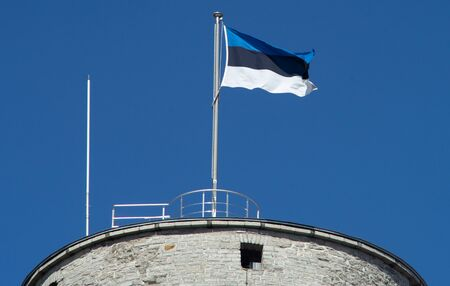 Estonian flag on the tower against the blue sky on a bright Sunny day Stockfoto