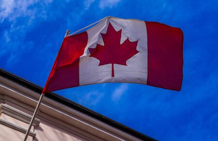 Canada flag on building against blue sky on bright Sunny day Stockfoto