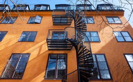 Black spiral fire escape against the wall of an orange building with large windows. Stockfoto