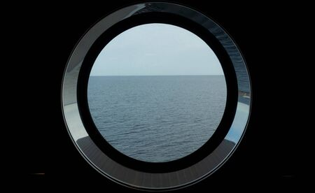 Sea view through the porthole of a passenger ferry in cloudy, calm weather