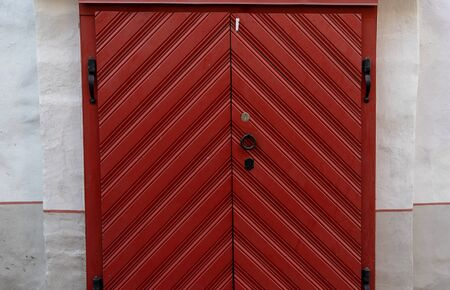 Large red wooden gate with black forged handles and hinges in an old building. Stockfoto