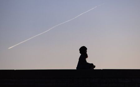 The silhouette of a meditating girl against the background of the condensation trail of a passing plane.