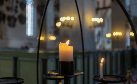 Burning candle on a metal candlestick in a Catholic Church