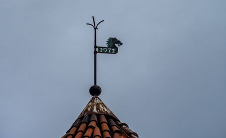 Weather vane with the inscription 1971 on the tiled roof of an old house in Tallinn