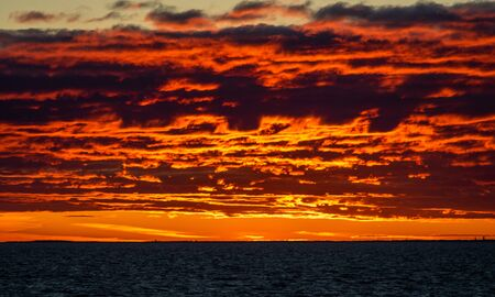 Clouds illuminated by the setting sun over the blue waters of the Baltic Sea. Stockfoto