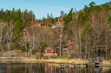 Picturesque summer houses painted in traditional falun red on dwellings island of the Stockholm archipelago in the Baltic Sea in the early morning. 免版税图像 - 139172540