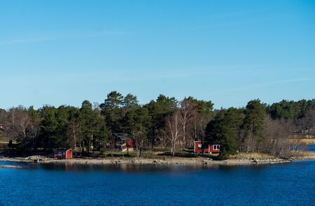 Picturesque summer houses painted in traditional falun red on dwellings island of the Stockholm archipelago in the Baltic Sea in the early morning.