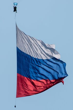 Skydiver in the sky with a giant flag of Russia against the blue sky.
