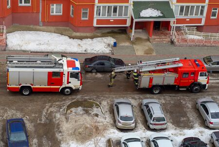 Fire engine in the courtyard of a multi-storey residential building in winter.