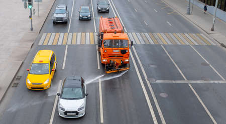 October 7, 2020, Moscow, Russia. Utility vehicles watering the street on a cloudy day.
