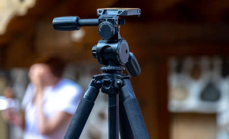 Large black professional tripod with swivel head on a busy street