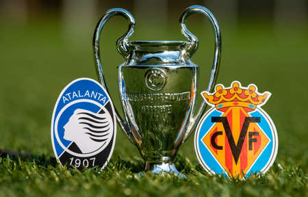August 27, 2021 Bergamo, Italy. The emblems of football clubs Atalanta BC and Villarreal CF and the UEFA Champions League Cup on the green lawn of the stadium. Editorial