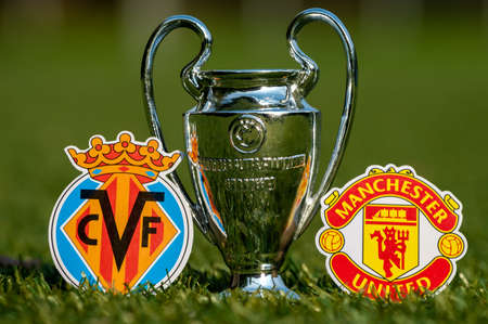 August 27, 2021 Villrreal, Spain. The emblems of football clubs Villarreal CF and Manchester United FC and the UEFA Champions League Cup on the green lawn of the stadium.